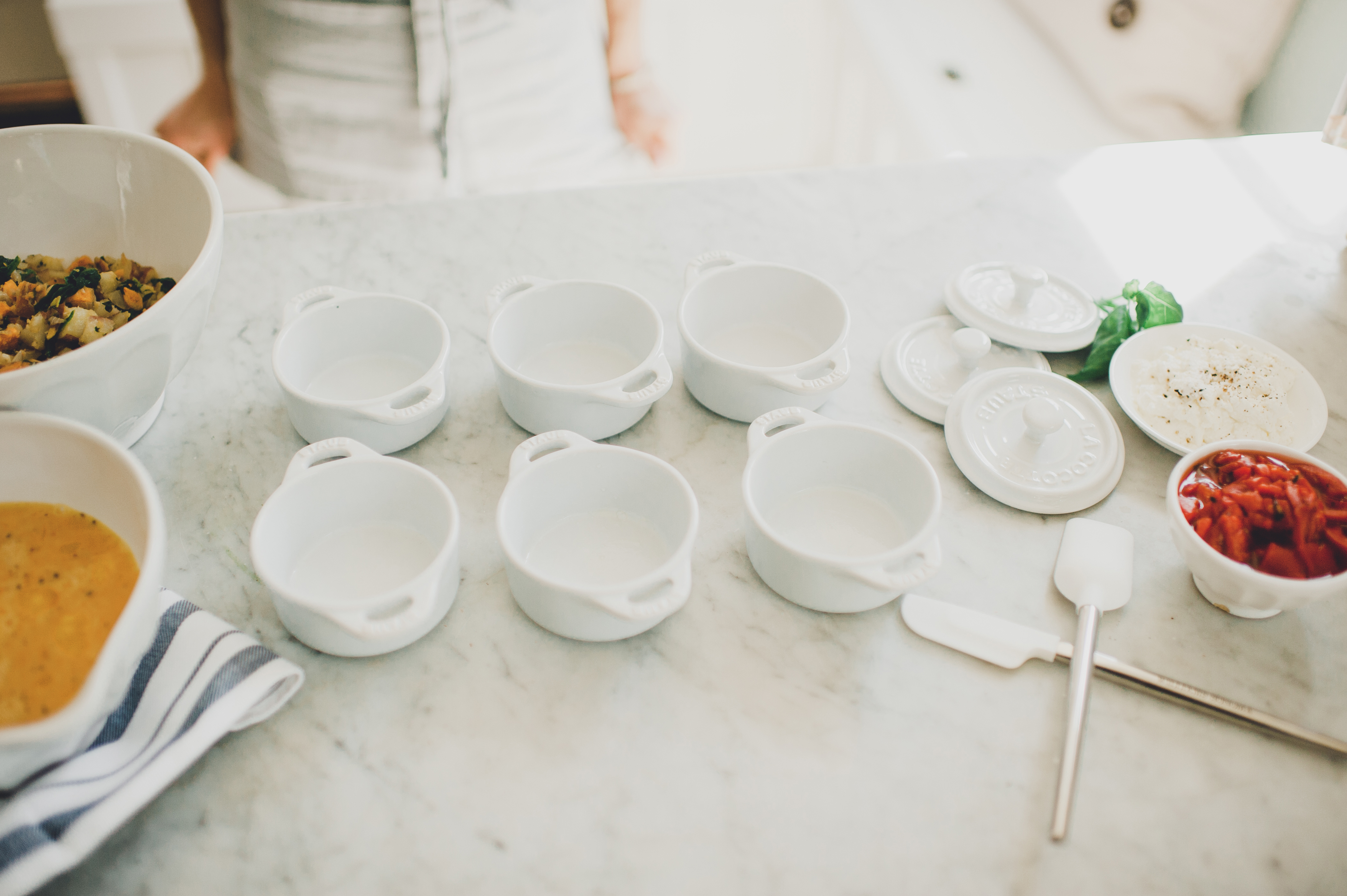 6 prepped small white baking dishes with ingredients